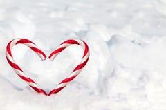 Bastones de caramelo de la forma del corazón en la nieve Imagenes de archivo