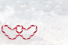 Bastones de caramelo dobles de la forma del corazón en la nieve Imágenes de archivo libres de regalías
