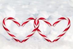Bastones de caramelo dobles de la forma del corazón en la nieve Fotos de archivo libres de regalías