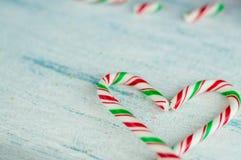 Bastones de caramelo en forma de corazón fondo azul, cierre para arriba foto de archivo libre de regalías