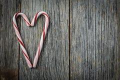 Bastones de caramelo en forma de corazón en un de madera rústico Foto de archivo