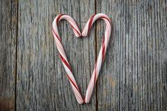 Bastones de caramelo en forma de corazón en una madera rústica Fotos de archivo libres de regalías