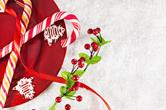 Bastones de caramelo en la placa roja con la decoración de la Navidad alrededor Imagenes de archivo