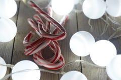 Bastones de caramelo en la tabla de madera Fotos de archivo