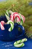 Bastones de caramelo en taza azul Imagen de archivo