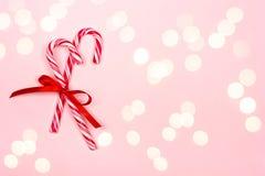 Bastones de caramelo de la Navidad en fondo rosado imágenes de archivo libres de regalías