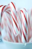 Bastones de caramelo rojos y blancos en taza de la Navidad Fotos de archivo