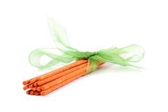 Bastoni arancioni di incenso legati con il legame verde su bianco Immagine Stock