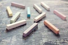 Bastoni colorati del gesso sul fondo dell'estratto del fondo della lavagna di nuovo alla scuola Immagine Stock Libera da Diritti
