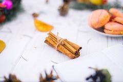 Bastoni di cannella avvolti con la corda su un fondo di legno bianco immagini stock libere da diritti