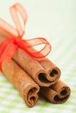 Bastoni di cannella con i bastoni di cannella rossi del nastro con il primo piano rosso del nastro fotografia stock