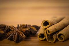 Bastoni di cannella e semi piccanti dell'anice stellato sulla tavola di legno immagine stock