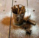 Bastoni di cannella in secchio su fondo di legno Fotografie Stock Libere da Diritti