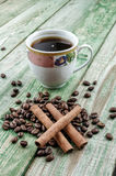 Bastoni di cannella sui chicchi di caffè con il caffè della tazza sulla tavola rustica verde Immagine Stock Libera da Diritti