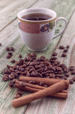 Bastoni di cannella sui chicchi di caffè con la tazza di caffè su vecchio fondo rustico Immagini Stock Libere da Diritti