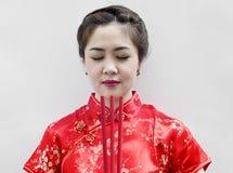 Bastoni di joss cinesi della holding della giovane donna Immagini Stock