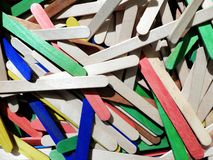 Bastoni di legno del mestiere dei colori differenti nell'ambito di luce dura immagine stock libera da diritti