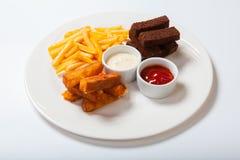 Bastoni di pesce con le patate fritte su un piatto bianco Immagini Stock Libere da Diritti