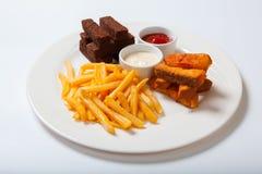 Bastoni di pesce con le patate fritte su un piatto bianco Immagini Stock