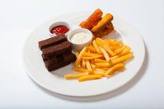 Bastoni di pesce con le patate fritte su un piatto bianco Fotografie Stock