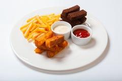 Bastoni di pesce con le patate fritte su un piatto bianco Fotografia Stock Libera da Diritti