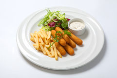 Bastoni di pesce con salsa, le patate fritte e la lattuga fresca dell'insalata su un piatto bianco Fotografia Stock