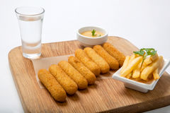 Bastoni di pesce su un bordo di legno con salsa e le patate fritte Fotografie Stock