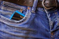 Bastoni di Smartphone da una tasca delle blue jeans immagini stock