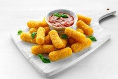 Bastoni impanati del formaggio della mozzarella con sugo al pomodoro e basilico Fotografia Stock