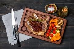 Bastoni la bistecca di manzo con i condimenti e le verdure arrostite Fotografie Stock
