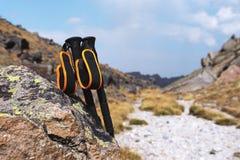 Bastoni professionali per la scalata della montagna vicino ad una pietra su un percorso dell'alta montagna contro un cielo blu e  Immagine Stock Libera da Diritti