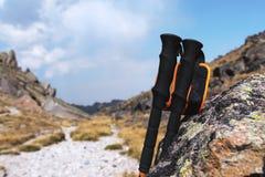 Bastoni professionali per la scalata della montagna vicino ad una pietra su un percorso dell'alta montagna contro un cielo blu e  Fotografie Stock Libere da Diritti
