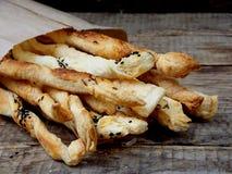 Bastoni salati della pasta sfoglia spruzzati con cumino e Nigella su un fondo di legno fotografia stock