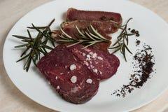Basturma da carne em uma placa com especiarias e alecrins imagens de stock royalty free