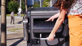 Basura ausente que lanza de la mano de la mujer en bote de basura público almacen de video