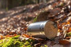 Basura de la lata en el primer del piso del bosque fotos de archivo