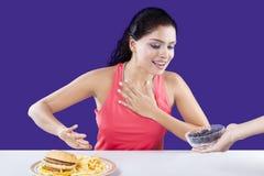Basura de la mujer para comer los alimentos de preparación rápida imagen de archivo libre de regalías