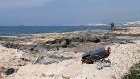 Basura del metal en la playa rocosa con el pescador y la nave en el fondo Contaminaci?n del mar metrajes