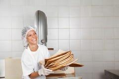 Basura del pan de Laughing While Holding del panadero Imagenes de archivo