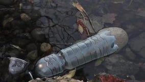 Basura en una orilla del lago, contaminación de agua metrajes
