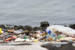 basura plástica de la basura en el paseo de la bahía que contamina el océano y el en fotografía de archivo