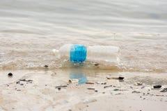 basura plástica de la basura en el paseo de la bahía que contamina el océano y el en foto de archivo libre de regalías