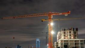 Basztowi żurawie przy budową w nocy mieście obraz stock