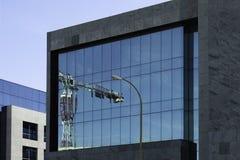 Basztowy żuraw odbijał w przodzie budynek biurowy Fotografia Stock