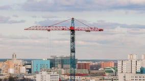 Basztowy żuraw pracuje na budowie wynosi ciężar, rozwój wielkomiejski zbiory
