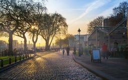 Basztowy park w słońce secie Rzeczny Thames boczny spacer z ludźmi odpoczywa wodą Londyn Zdjęcie Stock