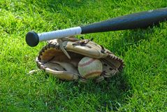 Bat,Ball, and Glove. Baseball bat, glove and baseball laying on grass field Stock Photo