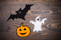 Bat, ghost and pumpkin jack-o-lantern made of felt on a wooden background. Halloween. Royalty Free Stock Photography