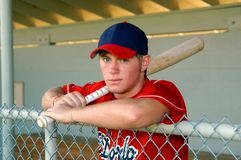 Bat in hand and ready to play. Young male baseball player leans over fence with a bat in his hands. He has on a red and navy uniform and hat royalty free stock image
