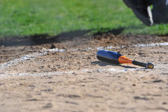 Bat left behind at home plate Royalty Free Stock Image